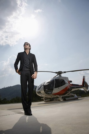 Businessman standing at helipad with helicopter in the background photo