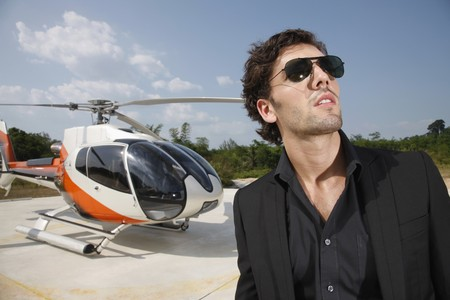 Businessman wearing sunglasses with helicopter in the background photo