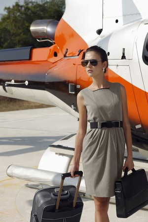 Businesswoman with luggage and briefcase walking from the helicopter photo