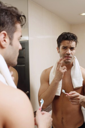 Man holding toothbrush while checking his teeth photo