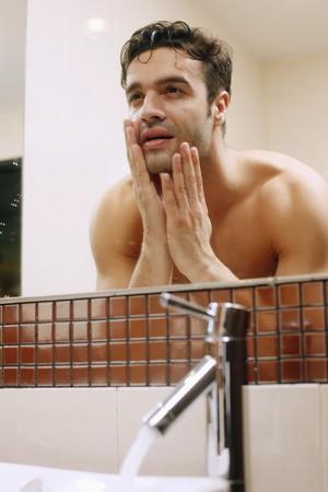 Man examining his face in the mirror Stock Photo - 7445971