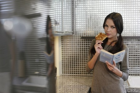 Woman eating toast while reading book photo