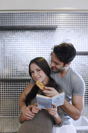 Man embracing woman and feeding her toast, woman holding a book photo