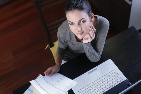 ukrainian ethnicity: Woman holding bills with laptop on the table