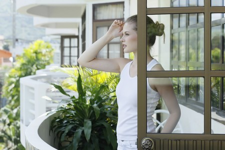 Woman standing at the balcony, looking out photo