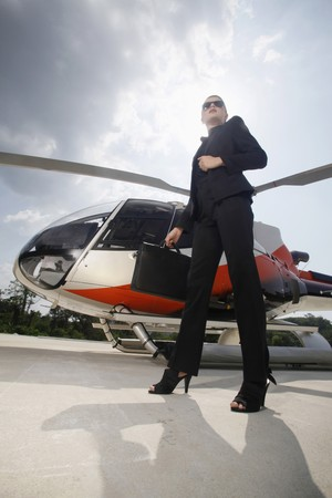 Businesswoman with sunglasses standing by helicopter photo