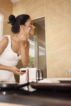 mujer maquillandose: Mujer aplicar maquillaje en el cuarto de ba�o  Foto de archivo