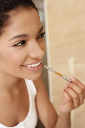 Woman applying lipstick photo