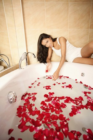 Woman playing with flower petals in a bathtub photo