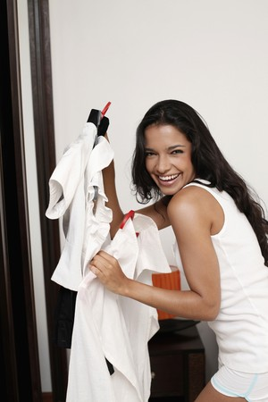 Woman choosing clothes from wardrobe photo