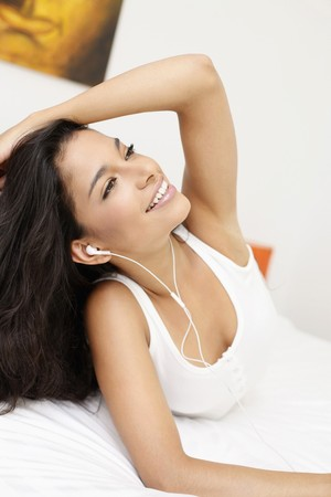 Woman listening to music while lying in bed photo