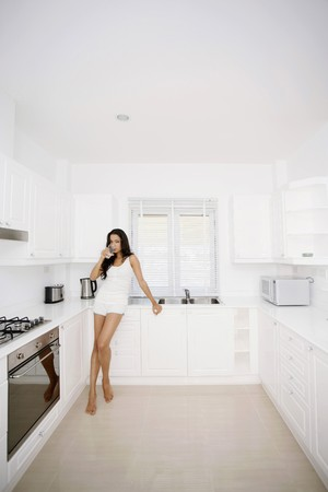 Woman drinking water in the kitchen photo