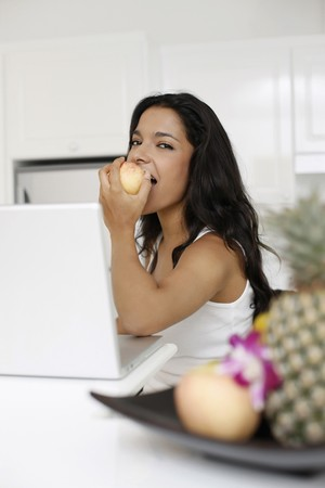 Woman eating apple while using laptop photo