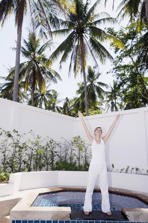 Woman standing by the poolside with her hands raised photo