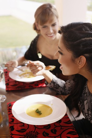 eating area: Women enjoying pumpkin soup  Stock Photo
