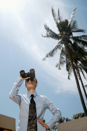Businesswoman looking through binoculars photo