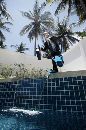 Businesswoman with scuba gear on jumping into swimming pool photo