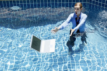 Businesswoman trying to save her laptop from the swimming pool Stock Photo - 7447016