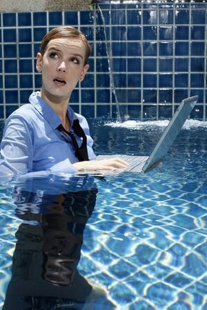 wet woman: Businesswoman using laptop in swimming pool