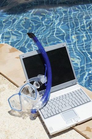 Laptop and diving mask by the pool side Stock Photo - 7446937