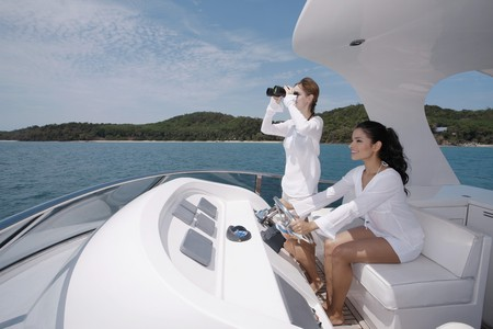 Woman steering yacht while another woman is looking through binoculars Stock Photo - 7446100