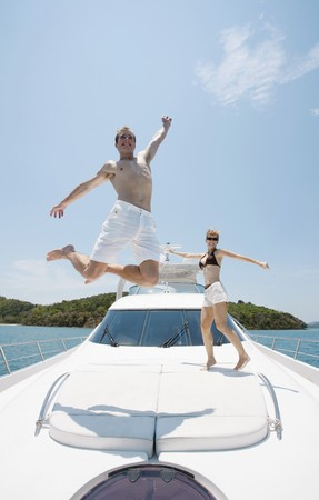 Couple jumping with arms raised on yacht Stock Photo - 7445858
