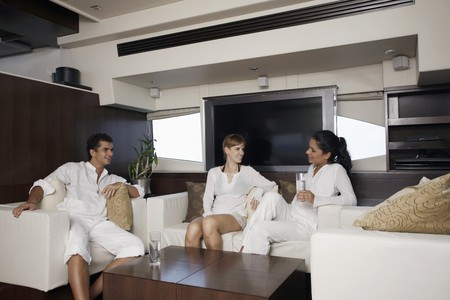 Man and women relaxing in yacht living room Stock Photo - 7446338