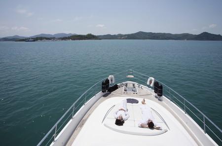 Couple sunbathing on yacht deck photo