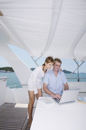 Couple using laptop on yacht with books on the table photo