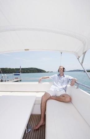 Man listening to headphones on yacht photo