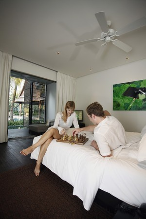 australian ethnicity: Couple playing chess in resort bedroom