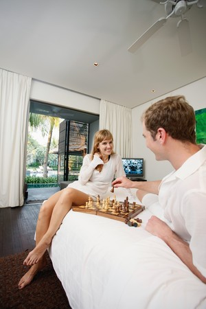 Couple playing chess in resort bedroom photo