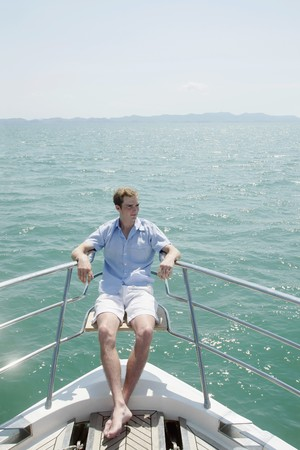 Man sitting on railing at the tip of the yacht photo