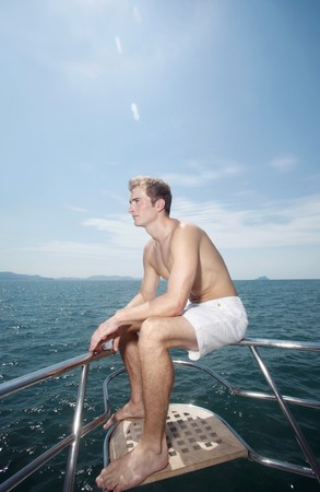 Man sitting on yacht's railing Stock Photo - 7446436