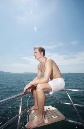 Man sitting on yacht's railing Stock Photo - 7446436