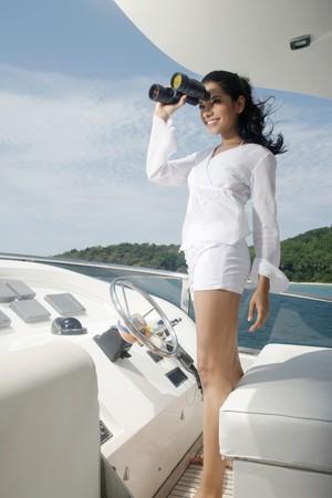 brazilian ethnicity: Woman looking through binoculars on yacht