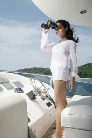 Woman looking through binoculars on yacht