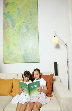 Girls reading together on sofa Stock Photo - 7446871