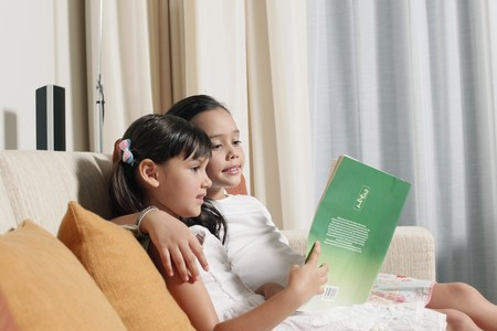 Girls reading together on sofa Stock Photo - 7446206