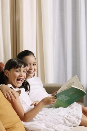 Girls reading together on sofa photo