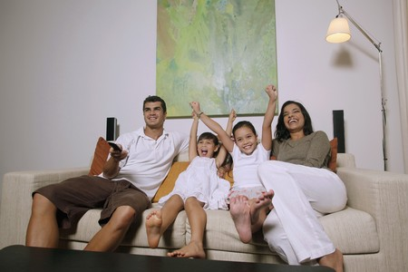 Family watching tv together, girls cheering with arms raised photo