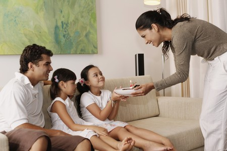 Woman surprising girl with chocolate cake, family sitting in the living room Stock Photo - 7446114