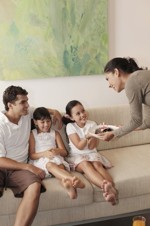 Woman surprising girl with chocolate cake, family sitting in the living room Stock Photo - 7446392