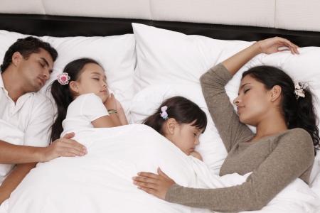 mujer en la cama: Familia durmiendo juntos en cama  Foto de archivo