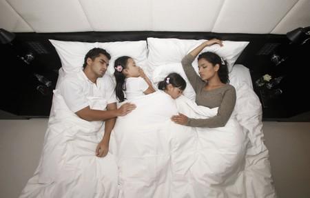 brazilian ethnicity: Family sleeping together on bed Stock Photo