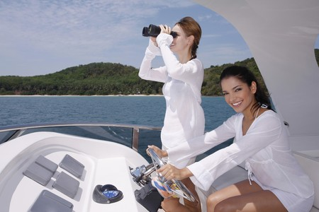 Woman steering yacht while another woman is looking through binoculars photo