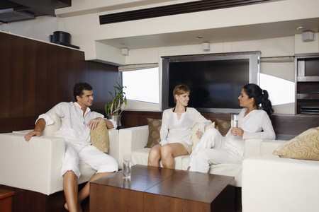 Man and women relaxing in yacht living room photo