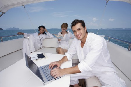 brazilian ethnicity: Man using laptop with woman listening to music and another woman reading book
