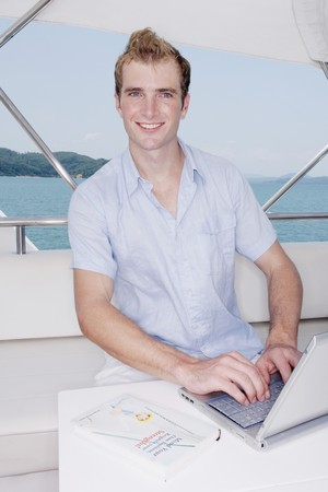 Man using laptop on yacht with book on the table photo