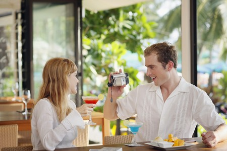 Man using video camera to record woman holding cocktail drink Stock Photo - 7478226